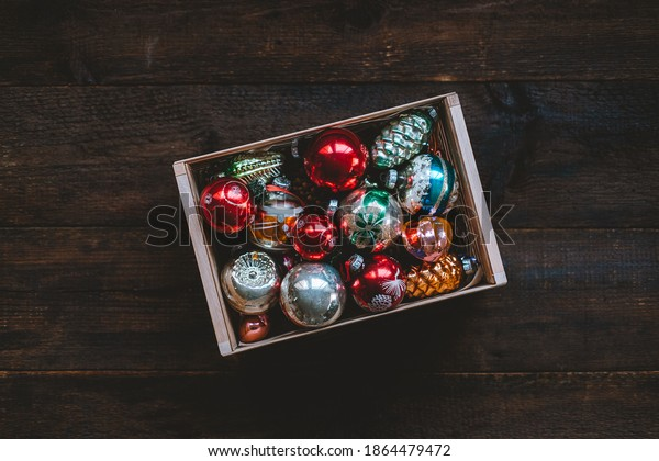 Vintage Christmas ornaments, antique retro Christmas glass baubles, balls in wooden box on rustic background. Old xmas decoration for Christmas tree in gif box