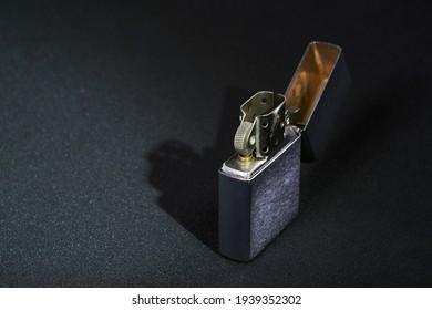 Vintage chrome steel gasoline lighter. Windproof lighter on a black background, close-up.