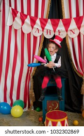 Vintage circus. Smiling funny baby girl in a red hat cylinder  in front of the circus tent.