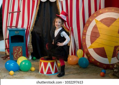 Vintage circus. Smiling funny and cute baby girl in a red hat cylinder in front of the circus tent.