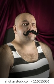 Vintage circus strongman with big mustache. Bald strong man with striped t- shirt. Part of larger vintage collection.