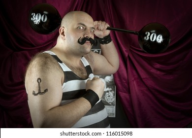 Vintage circus strongman holding big 300 lbs weights. Bald strong man in striped t- shirt lifting heavy weights. Vintage cinema circus scene. Part of larger vintage collection.