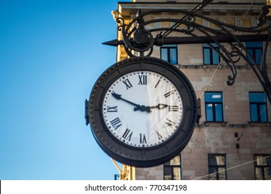 The vintage city clock in the street on a warm sunny day.