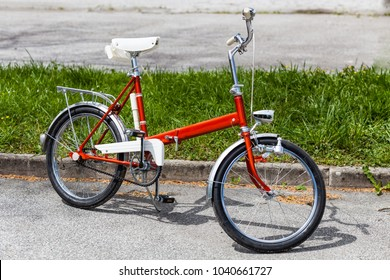 Vintage classic 1970s red folding bicycle bike in perfect condition parking on the road near grass