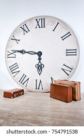 Vintage classic brown leather suitcases and big clock. World time in interior concept. Vacation travel holiday background