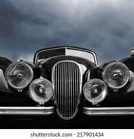 Vintage classic car front view with dark clouds