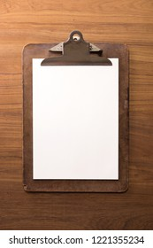 A vintage clipboard on a teak wood desk, with regular white blank paper.