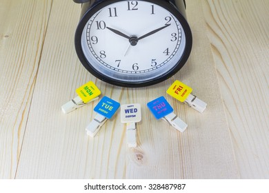 "Vintage clock and clothes pegs stuck with colorful square piece of wood with text ""happy (MON - FRI) everyday"" on wooden background"