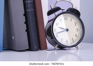 vintage clock and diary on table over colorful background wall.