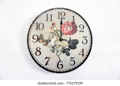 Vintage clock hanging on white wall shows twelve o'clock