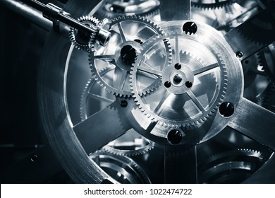 Vintage clock mechanism, close-up fragment with shiny gears, blue toned photo