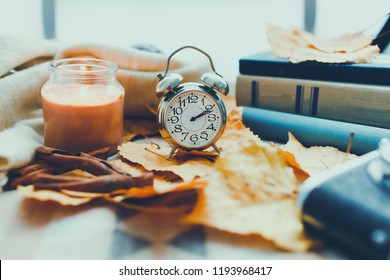 vintage clock on the background of autumn leaves Autumn shot with a candle and a clock lifestyle Autumn warmth Cozy home atmosphere beautiful composition with  clock camera and candle