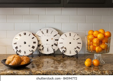 Vintage clocks on a counter with oranges and croissants