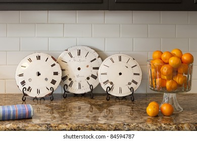 Vintage clocks on a counter with oranges and a towel