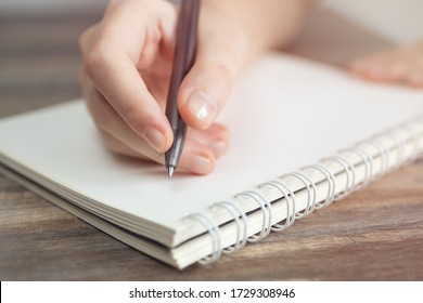 Vintage close up of female hand writing taking notes with pen in blank spiral notebook.