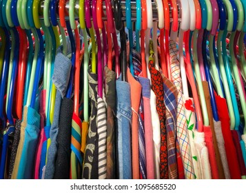 Vintage Clothes Shirts and Blouses Hanging on Clothing Rack on Colorful Hangers Various Patterns Prints Texture  at Pop Up Market