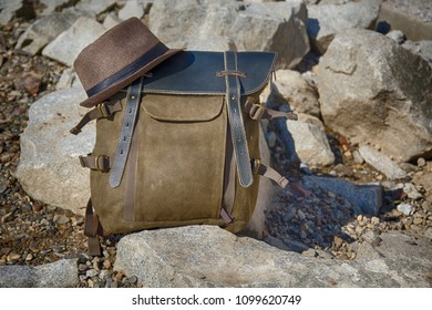 A vintage cloth-leather backpack stands on the stones, on top of the backpack lies a hat. HDR image.