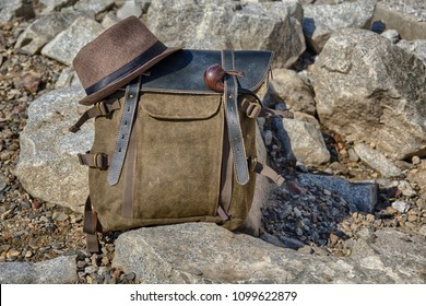 A vintage cloth-leather backpack stands on the stones, on top of the backpack lies a hat, a smoking pipe attached to the side. Travel or adventure or hiking kit