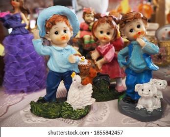 Vintage clown trinket and wooden toys on countertop at antique bazaar. Shopping at sunday flea market bazaar concept.