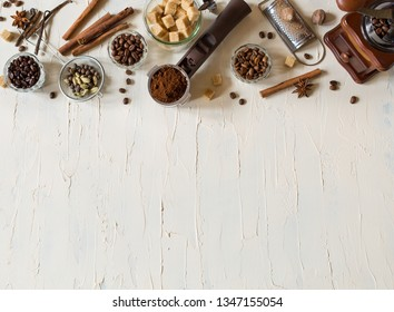 Vintage coffee banner with copy space. Coffee beans in bowls and spices ingredients for making drink, brown sugar cubes, cinnamon, nutmeg on old white background. Top view.