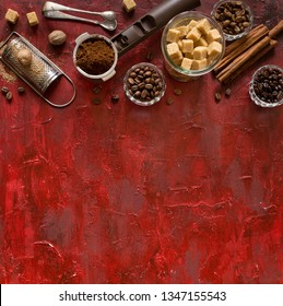 Vintage coffee banner with copy space. Coffee beans in bowls and spices ingredients for making drink, brown sugar cubes, cinnamon, nutmeg on old red background. Top view.