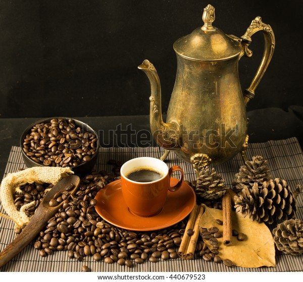 vintage of coffee beans on the ground, coffee in red cup,white flower,clove,pine, brass pitcher