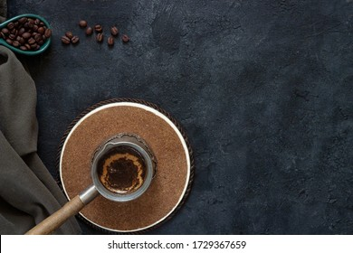 Vintage coffee maker with fresh coffee on a wooden stand on a dark background with coffee beans and green cotton fabric