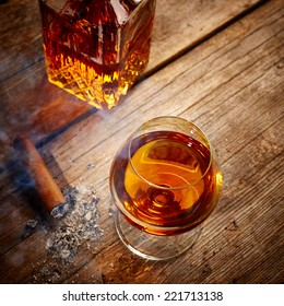 Vintage Cognac and cigar on wooden background