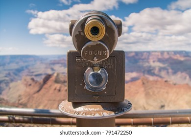 Vintage coin operated monocular overlooking the Grand Canyon National Park in Arizona, USA. Binocular telescope at observation deck for tourist viewer looking out on sunny day.