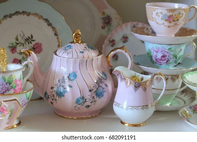 Vintage collection of bone china tea cups, jugs and teapots in pastel colors stacked on an old white wooden kitchen dresser