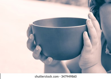 vintage color of a hungry children holding an empty bowl