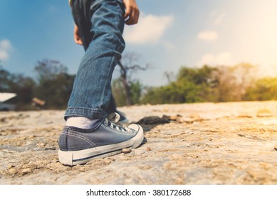 Vintage color, Kids leg in blue jean walking through the rough rocky land in the day time with strong sunlight. focus on shoe.