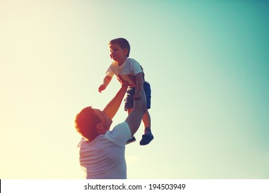 Vintage color photo happy joyful father having fun throws up in the air little boy child, family, travel, vacation, father's day - concept. Sunlight on the sunset background