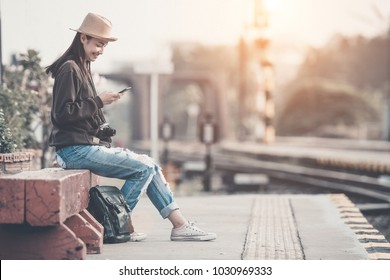 A vintage color photo of hipster asian girl use smartphone find a location in thailand during morning happy time