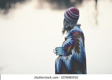 Vintage color portrait of young blonde woman in red cap and knitted colourful blanket enjoying sunset silence near lake with mug of tea - peace, calm and serenity concept, copy space