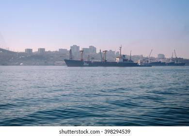 vintage color, ship with tugboat in port Vladivostok, Russia, golden horn