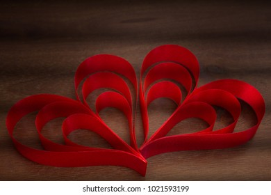 Vintage color style of red heart ribbons on a wood grain texture table with shadow lines inspires a theme of LOVE for the special loved one.