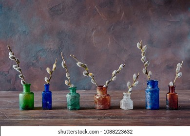 Vintage colored glass bottles with flowering willow branches, on an old wooden table. The background of the wall is Venetian plaster. Still life for home interior or decoration. With copy space