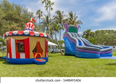 Vintage colorful small gazebo bounce house inflated next to a large blue twin falls inflated kids slip and slide. The sunny open tropical field is the perfect spot for children to play.