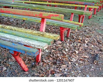 vintage colorful wooden bench heap, retro area in the park, autumn diversity