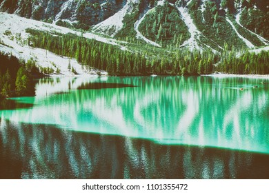 vintage colors of Braies lake in summer season with sunny light, shadow and mountain Croda del Becco in background, Dolomites - Italy