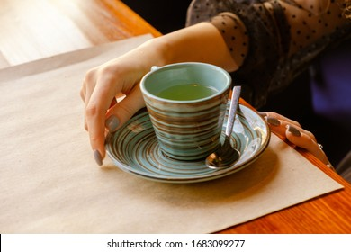 Vintage colors in the photo of hands and a cup of tea which stands on the table in front of a young girl who holds the bowl with her hand.