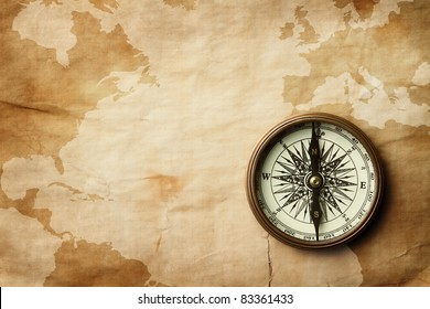 Vintage compass at old crumpled world map with copy space