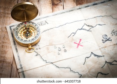 Vintage compass and treasure map on wooden table with vignette effect
