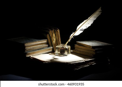 Vintage concept. Old fountain pen, books and inkwell on a black background