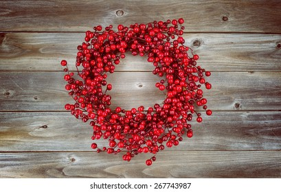 Vintage concept of a red berry holiday wreath on rustic wood