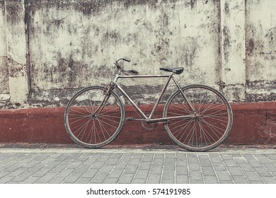 Vintage concept - retro bicycle leaning against old building.