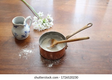 Photo of vintage copper saucepan, mini pitcher with blue flowers and white flowers on a wooden table