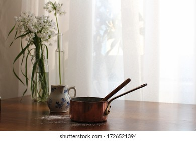 Photo of vintage copper saucepan, mini pitcher with blue flowers and a bouquet of white flowers on a wooden table