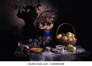 Vintage countryside still life: autumn leaves in a clay vase, basket of apples, pie, silver knife, antique tea cup, jar, glass of wine, hazelnuts, walnuts and chestnut on a table in light and shadows.